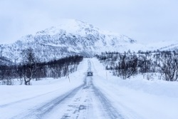 icy and snow covered road during a blizzard in the highland Tundra of northern Norway