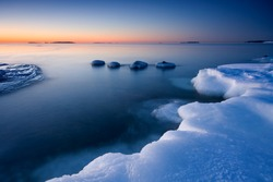 Icy beach and cold open water in the coast of Helsinki, Finland in early morning.
