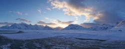 Icy cold snow capped mountain landscapes during sunrise near Fredvang village on the Lofoten Islands in Norway.