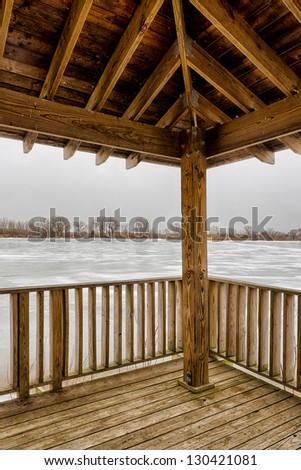 Icy frozen lake from the deck of a wooden gazebo