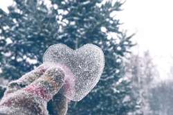 icy heart in hand. concept of love, romantic, February 14, Valentine's day. winter season. Christmas and New Year holiday background. frozen heart