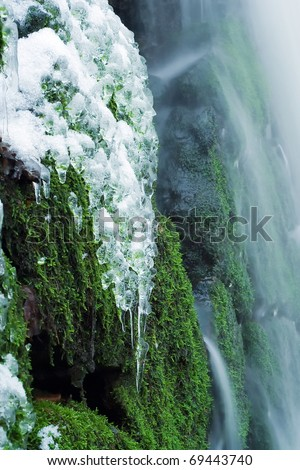 icy waterfall with mossy rocks
