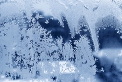 Icy window glass with beautiful ice pattern, close-up natural winter texture
