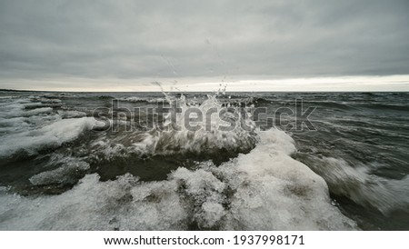 icy winter beach near the sea with frozen sand and ice blocks in the water. Cold dunes