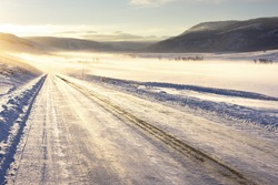 Icy winter road in the morning light in Yellowstone National Park.