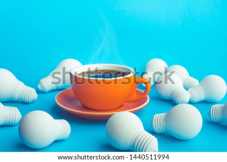 Idea and creativity concepts with hot coffee cup and light bulb on blue background.refreshment concepts