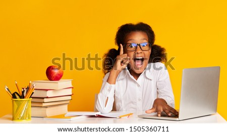 Idea Concept. Excited Afro School Girl Doing Homework At Laptop Raising Hand Pointing Finger Up Over Yellow Background In Studio. Panorama