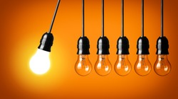 Idea concept on orange background. Perpetual motion with light bulbs