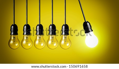 Idea concept on yellow background. Perpetual motion with light bulbs