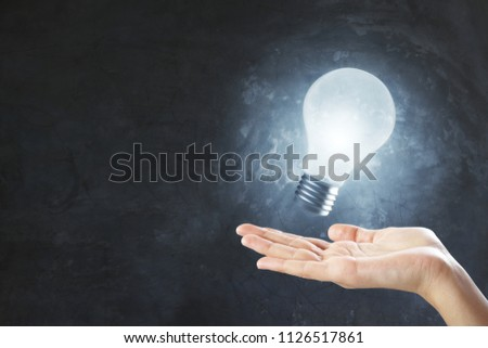 idea concept with glowing lightbulb and hand at grey concrete background.