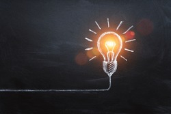 idea concept with innovation and inspiration, style symbol of creativity, brainstorm, creative idea, thinking. Lightbulb drawn by chalk representing ideas on dark background.