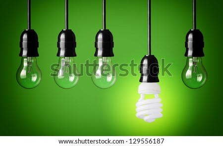 Idea concept with light bulbs and energy save bulb. Green background.