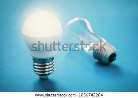 Idea concept with light bulbs. Illuminated LED lamp near reclining incandescent lamp, blue background #1056743204