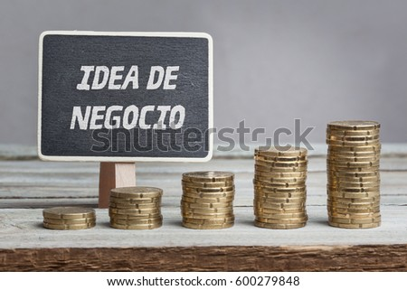 Shutterstock Idea de negocio, Spanish text for Business Idea, on black board behind growing stacks of money on wood table