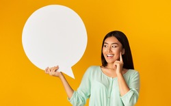 Idea. Excited Asian Girl Holding Empty Speech Bubble Standing Over Yellow Background. Studio Shot, Mockup