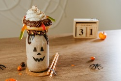 Idea for kids Halloween party table. Freak Monster shake decorated with chocolate donut and marmelade eye. Jack-o-lantern face on the jar. Copy space for text.