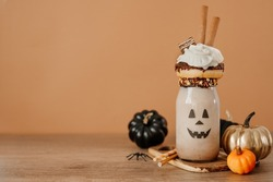 Idea for kids Halloween party table. Freak Monster shake decorated with chocolate donut and whipped cream on beige background. Jack-o-lantern face on the jar. Copy space for text.