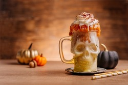 Idea for kids Halloween party table. Freak Monster shake in scull jar topping with whipped cream and caramel on wooden background. Selective focus.