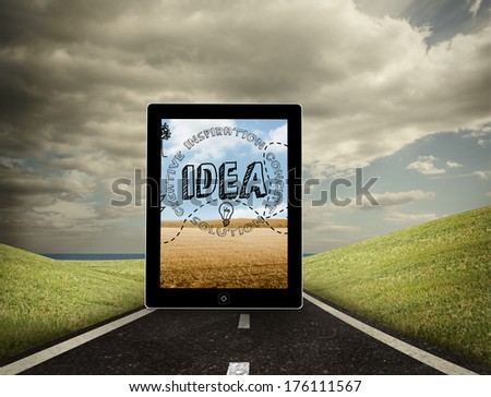 Idea graphic on tablet screen against highway under cloudy sky