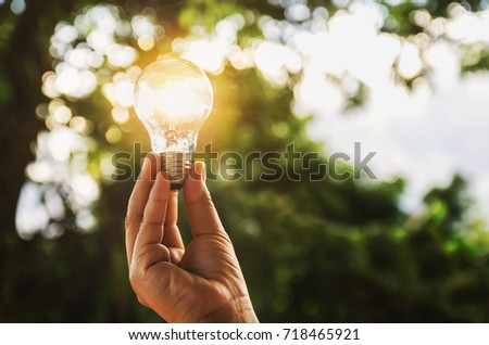 Photo of  idea solar energy in nature, hand holding light bulb concept