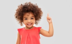 idea, warning and childhood concept - happy little african american girl pointing finger up over grey background