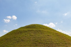 Ideal green round hill and blue sky with clouds above it. Krakus Mound, Krakow, Poland.