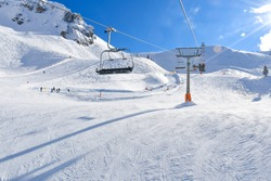 Ideal snow-covered ski runs for skiers in Alps. And a chair lift to the mountain.