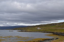 Idealistic Icelandic landscape containing water and beautiful clouds in the sky
