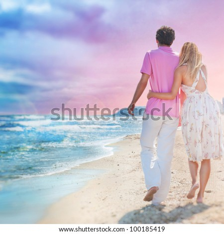 Idealistic poster for advertisement. Couple at the beach holding hands embracing and walking. Sunny day, bright colors. Photo from behind.  Europe, Spain, Costa Blanca