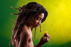 idealized picture of a rasta kid holding a flower, the color of the picture similar to the Jamaican flag