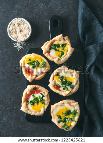 Ideas and recipes for healthy Vegan Shakshouka cups with vegan tofu eggs and turmeric yolk. Ready-to-eat. Puff filo pastry,tomato sauce and green parsley. Top view or flat lay. Copy space. Vertical
