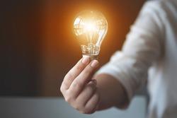 ideas creativity concept, woman holding light bulb in office.
