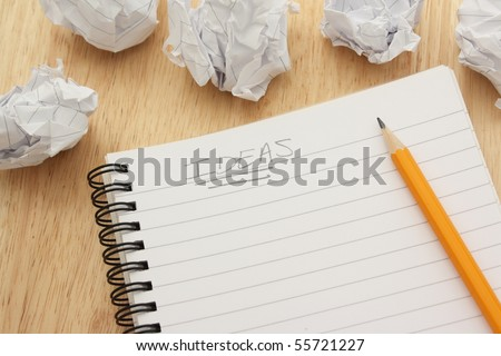 Ideas written on a blank notepad and surrounded by waste paper