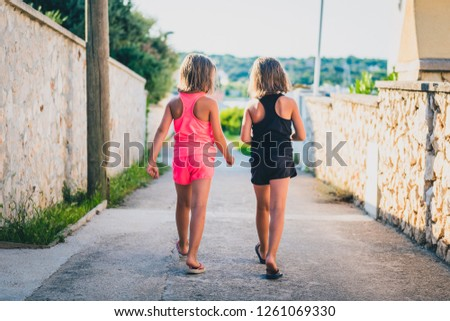 Identical twin girls sisters walking the island streets of Croatia. Children on summer vacation are waliking towards the beach through narrow Mediterranean streets of small island Silba, Croatia.