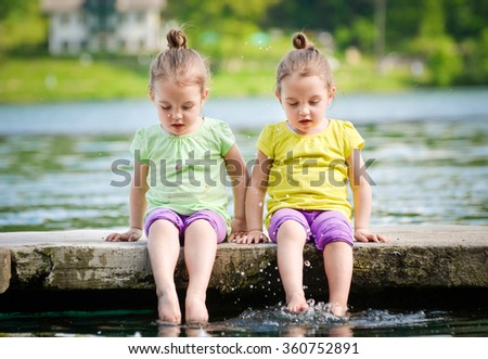 Identical twins girls are exercising on lake shore, sprinkling water. Children sitting on lake side, playing with water. Healthy and active children lifestyle.