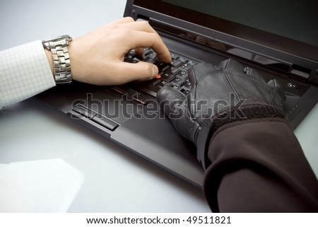 Identity theft with business man and hacker's hands on computer keyboard, internet crime - stock photo
