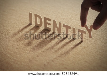 IDENTITY wood word on compressed board with human's finger at Y letter #525452491