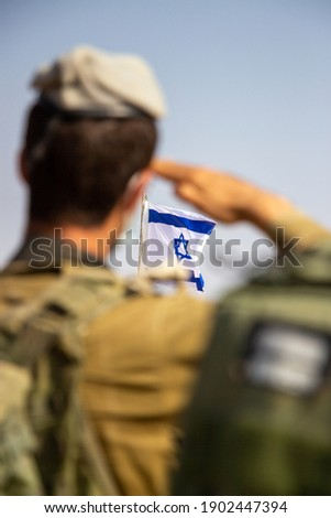 IDF officer saluting the Israeli flag