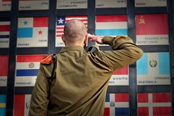 IDF soldier salutes the flags of countries that voted the UN for the establishment of the State of Israel, country names on flags translated in Hebrew to English. Concept: Independence Day Israel