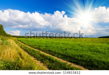 idilic rural landscape with green grass field, blue skywith sun, fluffy clouds and road in sunset light