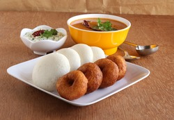 Idli or idly, is a healthy Indian, vegetarian, traditional and popular steam-cooked rice cakes, and vada, with bowls of chutney and sambar as side dishes.