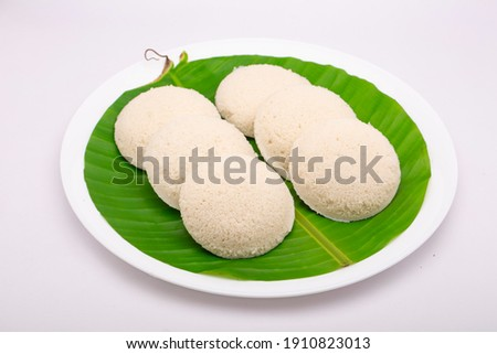 Idly or Idli, south indian main breakfast item which is beautifully arranged in a white plate lined with banana leaf on white background. Photo stock ©