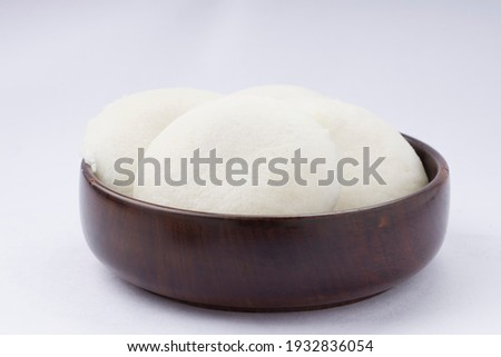 Idly or Idli, south indian main breakfast item which is beautifully arranged in a wooden round bowl placed on white background. Photo stock ©