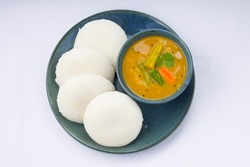 Idly or Idli, south indian main breakfast item which is beautifully arranged in aqua colour plates with a small bowl of sambar placed on white background.