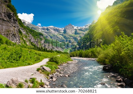 Idyllic alpine valley with mountain river and hiking trail in sun rays. Sixt Fer a Cheval national reserve, France.