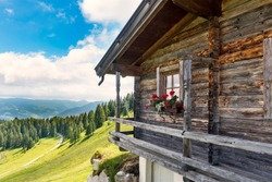 Idyllic alpine wooden mountain hut scenery in Austrian alps, forest trees and  green meadows, sunny day, blue sky
