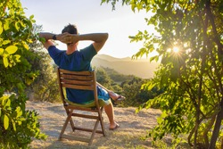 idyllic and rural scene. A man chilling and resting after hiking sitting on a wooden chair and looking at the sunset next to his house in the mountains. Congost De Mont Rebei, Lleida, Spain