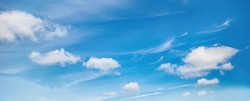 Idyllic Blue Sky with soft clouds in summer sunny day. Panoramic Bright Nature Background for Design. Beautiful Cloudscape texture. Wide Angle Natural Wallpaper or Web banner With Copy Space