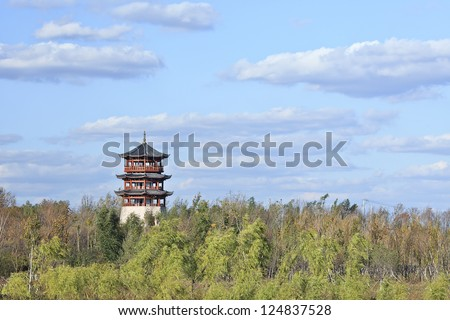 Idyllic Chinese pagoda surrounded by green trees.