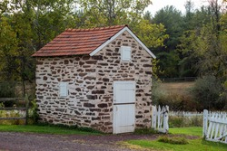 Idyllic country scene with a colonial stone spring house, by a white garden gate and idyllic Autumn woodland landscape background.
